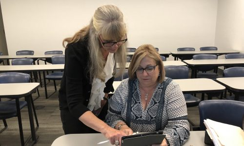 Staff member receiving one-pon-one ipad training in a classroom setting. Office of Instructional Technology